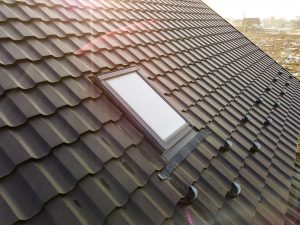 Close-up of new attic plastic window installed in shingled house