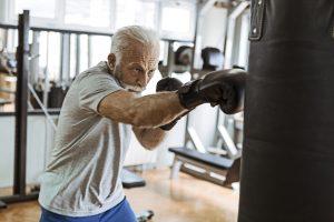 Senior in gym training boxing